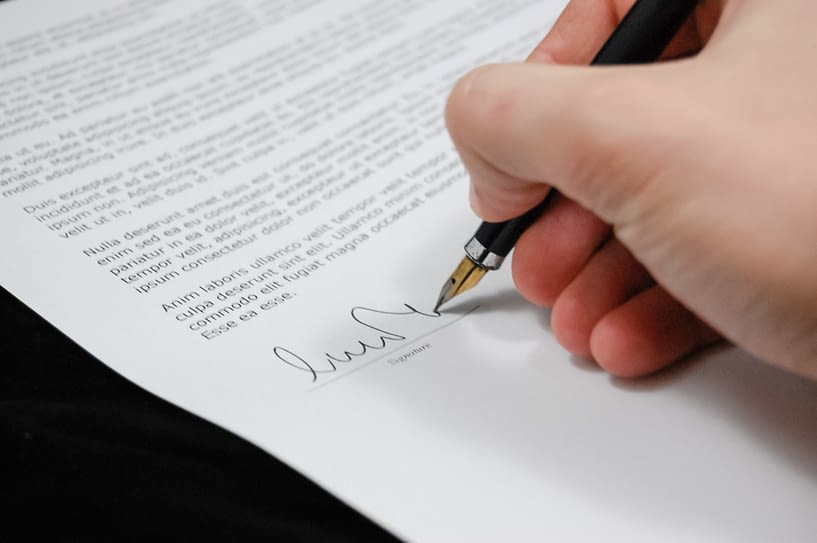 hand signing contract with pen